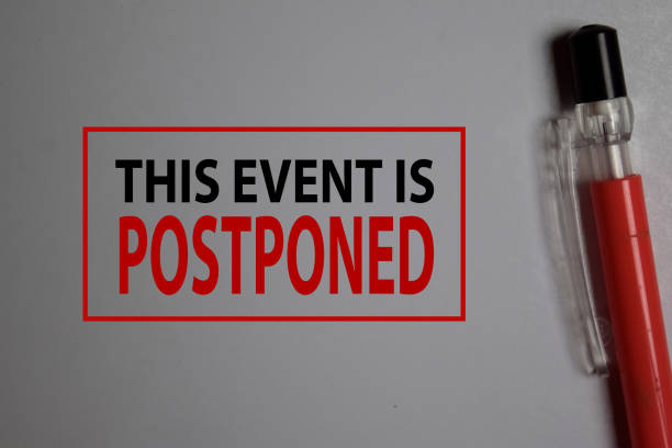 This Event is Postponed write on a book isolated on Office Desk. stock photo