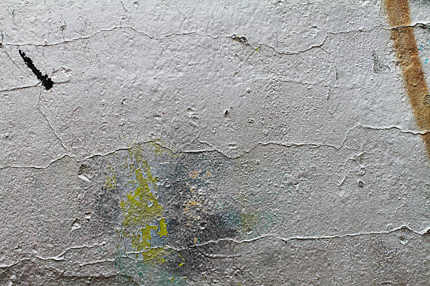 ageing sprayed graffiti silver on plaster wall texture - whiteway graffiti stock photos and pictures