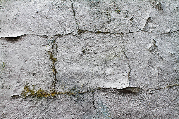 grunge ageing sprayed graffiti silver on plastered wall texture - whiteway graffiti stock photos and pictures