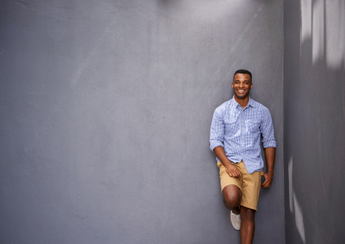 A handsome young man leaning against a gray wall