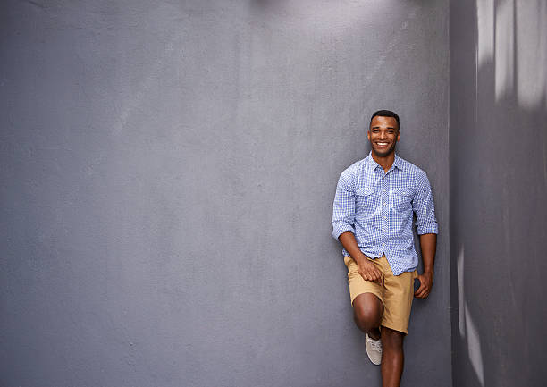 This guy just knows what's hip and happening A handsome young man leaning against a gray wall shorts stock pictures, royalty-free photos & images