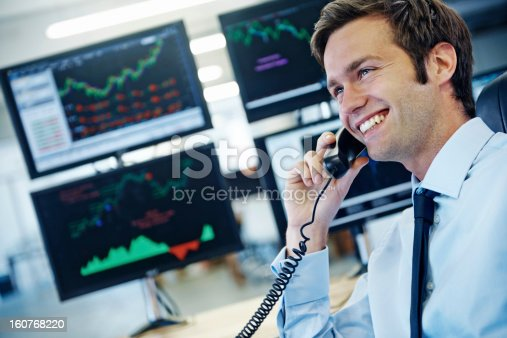 Profile shot of a smiling young businessman talking on the phone while sitting in front of monitors displaying financial information