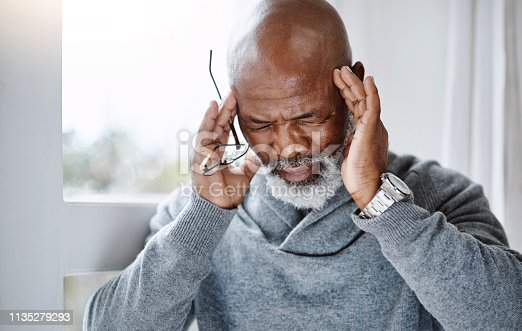 Shot of a handsome senior man suffering with a headache at home