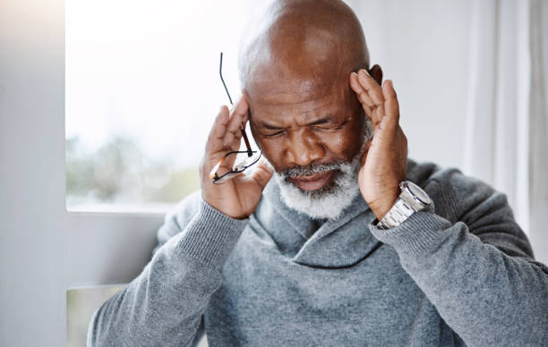 This headache is unbearable! Shot of a handsome senior man suffering with a headache at home headache stock pictures, royalty-free photos & images