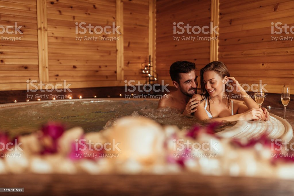 This hot tub feels amazing Shot of a beautiful young couple enjoying in a hot tub Adult Stock Photo