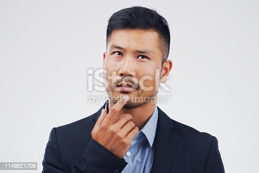 Studio shot of a man looking thoughtful against a gray background