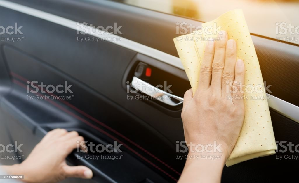 This image is a picture of wiping the car with a yellow microfiber cloth by hand. Car wash concept. stock photo
