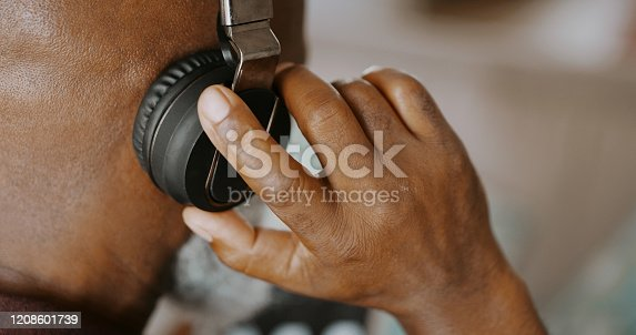 Cropped shot of an unrecognizable man sitting alone on his sofa and listening to music through headphones