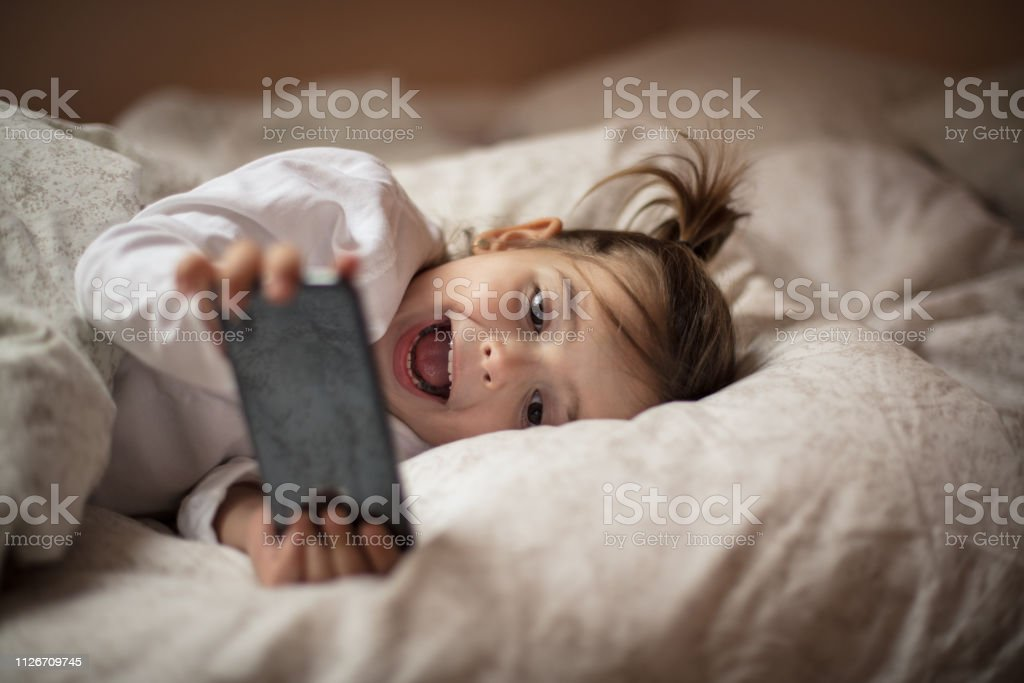 This is a lot of fun. This is a lot of fun. Little girl using smart phone in the bed. Close up. 2-3 Years Stock Photo