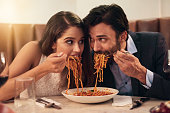Shot of a young couple sharing a plate of spaghetti during a romantic dinner at a restaurant