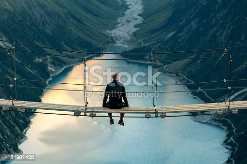 Rear view of Man sitting on rope bridge looking at Mountain landscape. Lonely man enjoying the view from Schlegeis Stausee (Schlegeis Lake) in Tyrol, Austria. Man looking at Schlegeis glacier and beautiful blue lake in the mountains of Tirol, Austria.