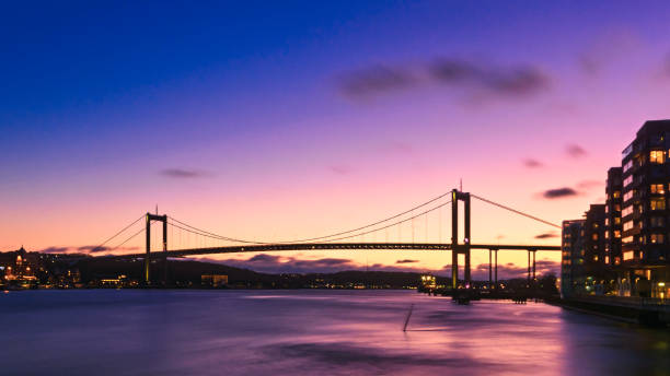 This is a suspension bridge in Gothenburg, Lnadmark of swedish architecture. Shot from boat during blue hour. Setting sun creating beautiful colors. stock photo
