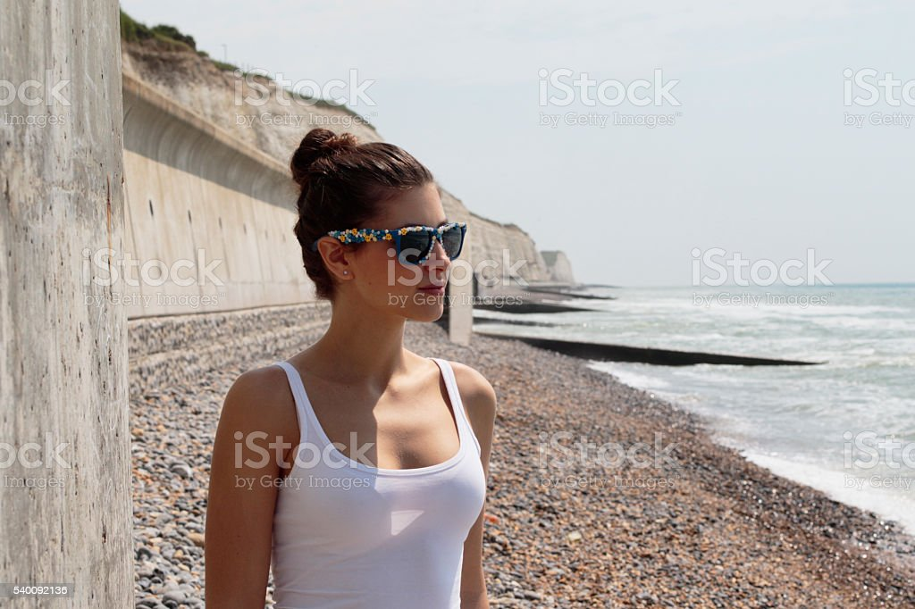 Waist up portrait Russian outdoor girl with sunglasses groynes background stock photo