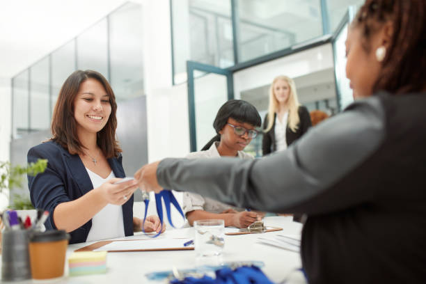 This is all you need Shot of a cheerful businesswoman handing over a access card to a client to attend a seminar during the day security pass stock pictures, royalty-free photos & images