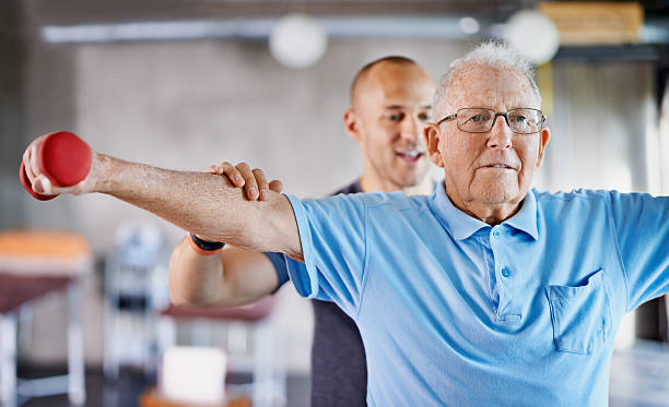This is all you now! Shot of a physiotherapist helping a senior man with weights alternative therapy stock pictures, royalty-free photos & images