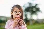 Cropped shot of a little girl enjoying a cupcake outside