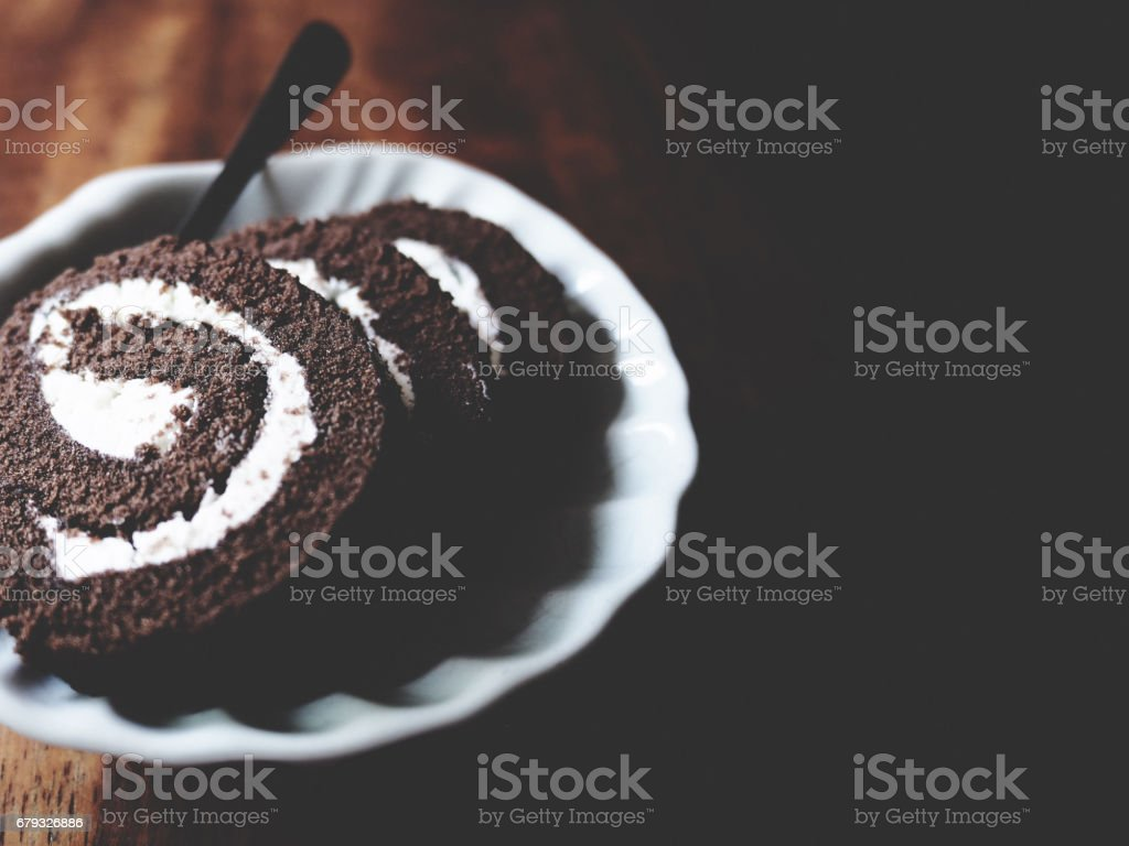 This is chocolate roll in white plate above wooden, soft tone royalty-free stock photo