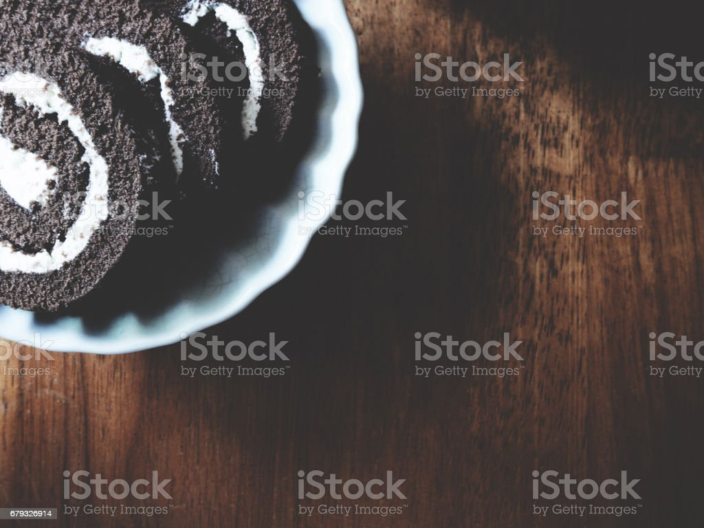 This is chocolate roll in white plate above wooden, soft tone stock photo