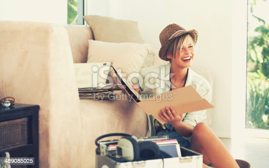 A beautiful young woman laughing while sitting and holding a record