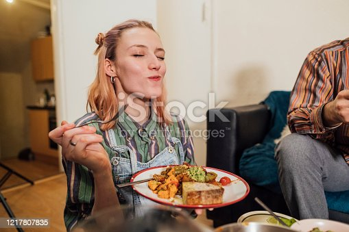 Woman eating a home made vegan dish. Her and her friends have cooked creole aubergines and quinoa with sweet potatoes, peppers and avocado puree. She has her eyes closed and is enjoying the meal.