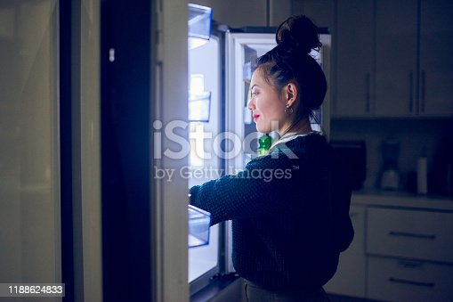 Cropped shot of an attractive young woman looking in her fridge for a midnight snack at home