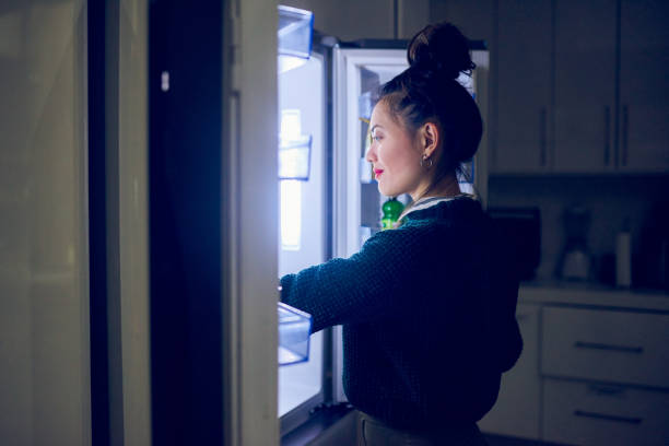 This is exactly what I'm craving Cropped shot of an attractive young woman looking in her fridge for a midnight snack at home midnight stock pictures, royalty-free photos & images