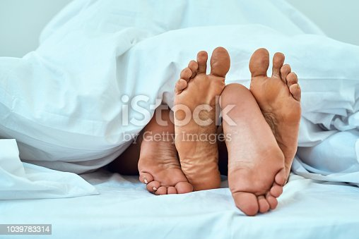 Shot of a couple's feet poking out from under the bed sheets