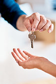 Shot of a unrecognizable person receiving a key from another person inside during the day