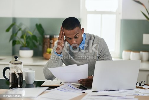Shot of a young man looking stressed out while going through paperwork at home