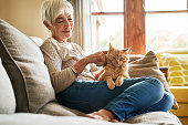 Cropped shot of a happy senior woman sitting alone and petting her cat during a day at home