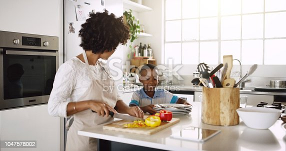 Cropped shot of young beautiful mother making food with her son's help in the kitchen at home
