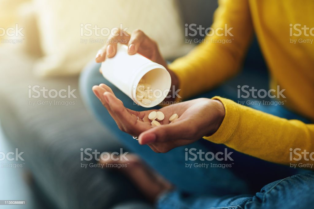 This is how I get through the day Cropped shot of a young woman taking medication at home 20-29 Years Stock Photo