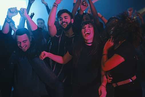 Cropped shot of a group of energetic young friends dancing at a party in a nightclub