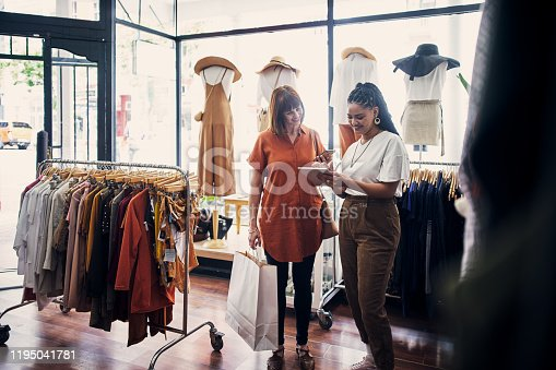 Shot of a shop assistant using a digital tablet while assisting a customer in a boutique