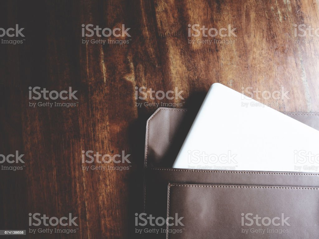 this is laptop on wooden table, minimal style, soft tone stock photo