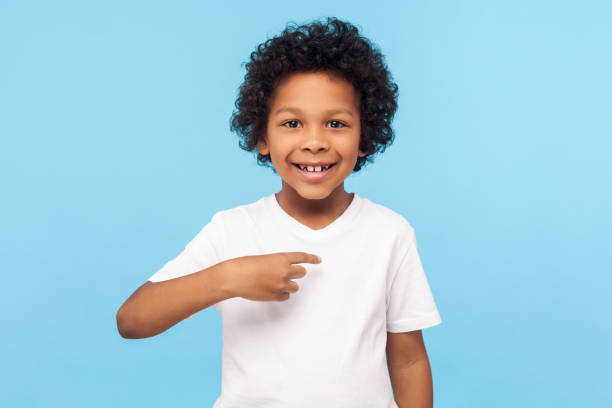 This is me. Portrait of happy preschool curly boy in T-shirt joyfully looking at camera and pointing to himself stock photo