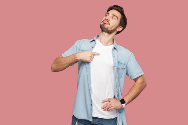eu sou assim. retrato do homem novo barbudo considerável arrogante orgulhoso na posição ocasional azul da camisa do estilo, olhando afastado e apontando-se. - 25 30 anos - fotografias e filmes do acervo