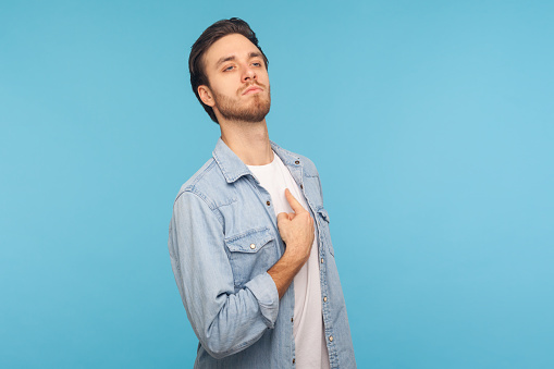 This is me! Portrait of selfish narcissistic man in worker denim shirt pointing himself, looking with pride arrogance, feeling self-important and famous. indoor studio shot isolated on blue background
