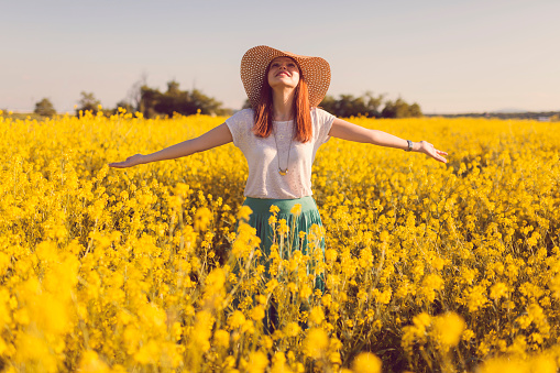 Beautiful, russet young woman with a hat standing in the middle of the flower meadow, surrounded by yellow flowers, with her arms outstretched