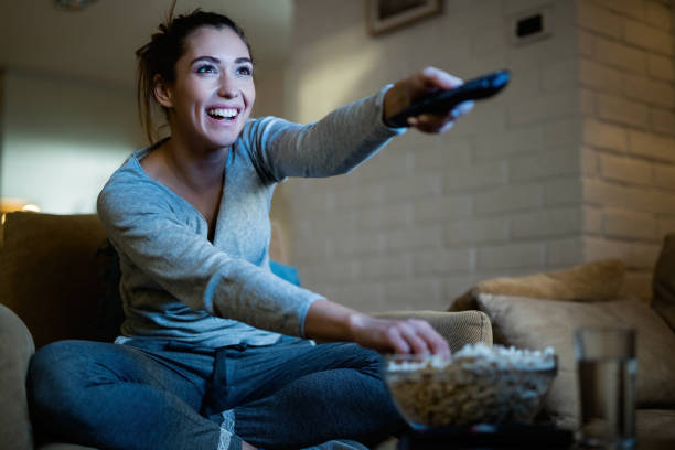 This is my favorite episode! Young happy woman changing channels with remote control while watching TV and eating popcorn in the evening at home. changing channels stock pictures, royalty-free photos & images