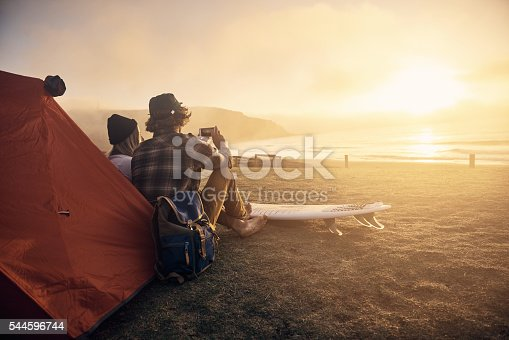 Shot of two surfers sitting by a tent while waiting for the perfect wave