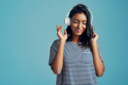 Cropped shot of a beautiful young woman wearing headphones against a blue background