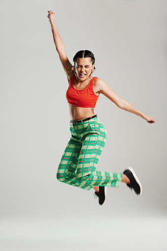 Studio shot of a stylish young woman jumping against a grey background