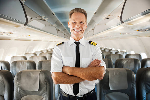 This is my plane. Confident male pilot in uniform keeping arms crossed and smiling while standing inside of the airplane cabin crew stock pictures, royalty-free photos & images