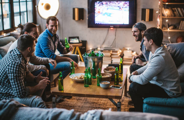 This is night for win, I can feel it Group of friends watching basketball game on tv at home. man cave couch stock pictures, royalty-free photos & images