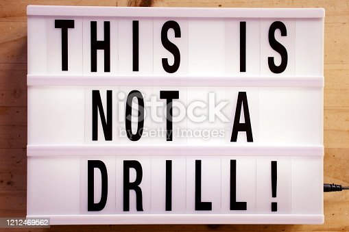 Words 'This Is Not A Drill' in a Light Box Trend for a Climate Change Theme.