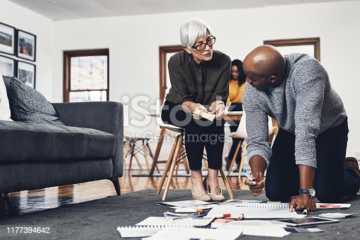 Full length shot of two businesspeople looking over paperwork while working on the floor of their office