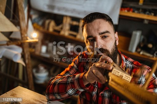 Photo of young man makes a model of a ship in his workshop