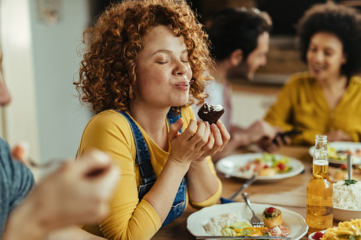 Young woman with eyes closed enjoying in taste of food while eating with friends at dining table.