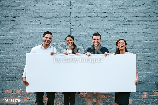 Portrait of a group of businesspeople holding a blank placard against a grey wall outside